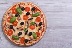 Mushroom pizza with olives, tomatoes and basil on the table Royalty Free Stock Photo