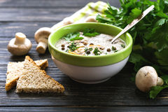 Mushroom puree soup with allspice, parsley, champignons and toasts. On wooden background. Selective focus royalty free stock images