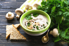Mushroom puree soup with allspice, parsley, champignons and toasts. On wooden background. Selective focus royalty free stock image