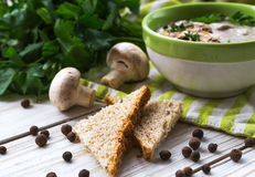 Mushroom puree soup with allspice, parsley, champignons and toasts. On wooden background. Selective focus royalty free stock photography