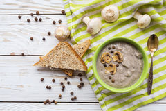 Mushroom puree soup with allspice, parsley, champignons and toasts. On wooden background. Selective focus stock images