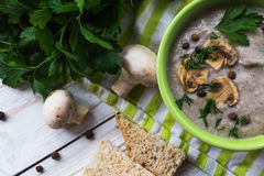 Mushroom puree soup with allspice, parsley, champignons and toasts. On wooden background. Selective focus stock photography