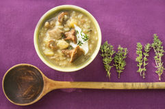 Mushroom rice ragout with old wooden spoon on lilac Royalty Free Stock Image