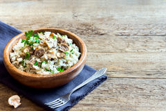 Mushroom risotto. With parsley in wooden bowl over rustic background with copy space Royalty Free Stock Photo