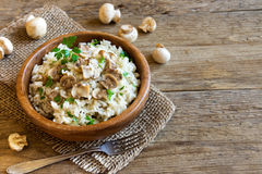 Mushroom risotto. With parsley in wooden bowl over rustic background with copy space - healthy vegetarian food Royalty Free Stock Image