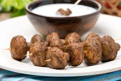 Mushroom skewers with yogurt sauce, close-up Stock Images