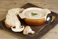 Mushroom soup. Bowl of hot mushroom soup and crusty bread on a wooden table Royalty Free Stock Image