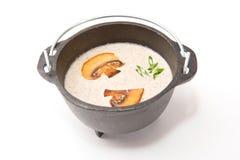 Mushroom soup in brutal rustic black metal pot on white Stock Images