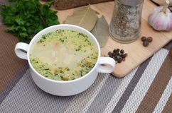 Mushroom soup with croutons in a white dish is on a wooden table Royalty Free Stock Images