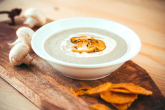 Mushroom soup. Plate of mushroom cream soup served with  toasts on wooden board Stock Images