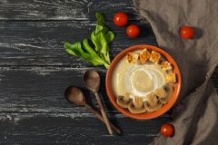 Mushroom soup puree with croutons on a rustic background with wooden spoons Stock Photo