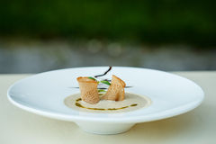 Mushroom soup puree with garlic croutons in a large plate. Bowl of vegetarian mushroom puree soup in a large plate on bokeh background of greens Stock Photo