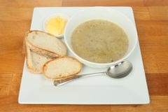 Mushroom soup on a tabletop. Mushroom soup with bread and butter on a wooden tabletop royalty free stock photo