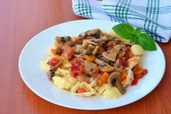 Mushroom stew with vegetables and pasta. Decorated with basil leaf royalty free stock photo