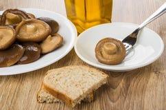 Mushroom strung on fork in saucer, vegetable oil and bread. Mushroom strung on fork in white saucer, bottle of vegetable oil and bread on wooden table Stock Photography