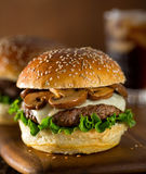 Mushroom Swiss Burger. A delicious gourmet hamburger topped with swiss cheese and fried mushrooms on a rosemary sesame seed bun Stock Photo