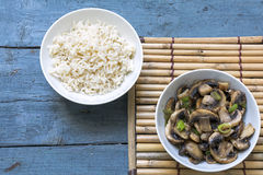 Mushroom vegetables and cooked rice in bowls on a bamboo mat and Royalty Free Stock Photo