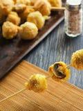 Mushrooms in batter. Recipe mushrooms in tempura on skewers pile of balls in the side Stock Photography