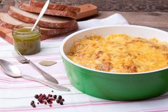Mushrooms and cabbage casserole in frying pan with bread, pesto, pepper. Casserole with mushrooms and cabbage in frying pan with fresh bread, pesto, pepper and Stock Photo