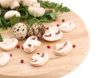 Mushrooms champignon and quail eggs on platter. Royalty Free Stock Photo