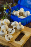 Mushrooms champignons on the kitchen board Royalty Free Stock Image