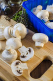 Mushrooms champignons on the kitchen board Royalty Free Stock Photos