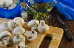 Mushrooms champignons on the kitchen board Stock Photos