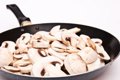 Mushrooms cutted to pieces on the frying pan Royalty Free Stock Photo