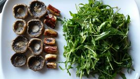 Mushrooms. Dietary dish of mushrooms and arugula Royalty Free Stock Photography