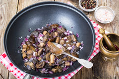 Mushrooms fried with red onion in frying pan Stock Photography