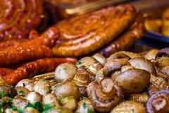 Mushrooms and fried sausages 1 Stock Photos