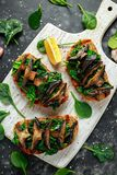 Mushrooms and garlic sauteed spinach toasts With lemon wedges. healthy food. royalty free stock photos