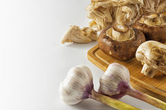 Mushrooms and garlic on white background. Mushrooms and garlic on a cutting Board Royalty Free Stock Images