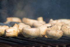 Mushrooms on the grill. Close-up of a row of mushrooms, getting cooked on the grill royalty free stock photography