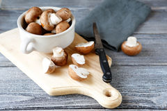 Mushrooms and knife on  cutting board Royalty Free Stock Photography