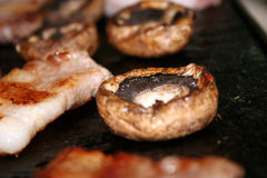 Mushrooms and Korean BBQ. Mushrooms and bacon (korean style BBQ) fried on a pan Stock Photos
