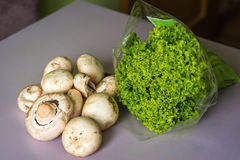 Mushrooms and lettuce on a table. Raw and fresh mushrooms and lettuce on the table Stock Photos