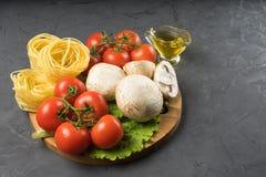 Mushrooms mushrooms, lettuce, tomatoes and spaghetti on stone table. Mushrooms mushrooms, lettuce, tomatoes and spaghetti on table Royalty Free Stock Photo