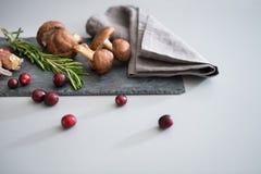 Mushrooms lingonberries and rosmarinus on table Stock Image