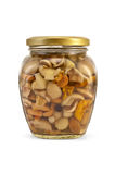 Mushrooms marinated. Assorted marinated mushrooms in a glass jar with a light shade on white background Stock Image