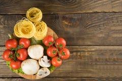Mushrooms mushrooms, lettuce, tomatoes and spaghetti on wooden table. Mushrooms mushrooms, lettuce, tomatoes and spaghetti on table Stock Photography