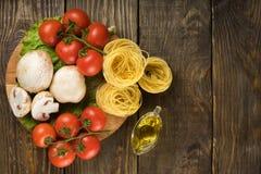 Mushrooms mushrooms, lettuce, tomatoes and spaghetti on wooden table. Top view. Mushrooms mushrooms, lettuce, tomatoes and spaghetti on table Stock Image