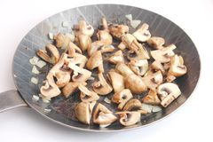 Mushrooms and onions in a pan Stock Images