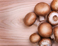 Mushrooms over wooden background. Baby Bella Royalty Free Stock Images