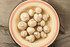 Mushrooms on a plate on wooden background, top view Royalty Free Stock Image