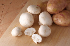 Mushrooms and potatoes. Raw mushrooms (agarics) and potatoes on wood board. Selective focus Royalty Free Stock Image