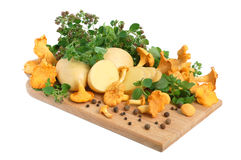 Mushrooms with potatos. Yellow chanterelle mushrooms with marjoram leaves and potatos on a cutting board Stock Images