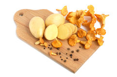 Mushrooms with potatos. Yellow chanterelle mushrooms with potatos on a cutting board Royalty Free Stock Photos