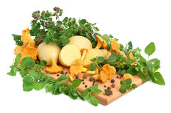 Mushrooms with potatos. Yellow chanterelle mushrooms with marjoram leaves and potatos on a cutting board Royalty Free Stock Photo