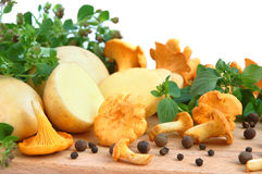 Mushrooms with potatos. Yellow chanterelle mushrooms with marjoram leaves and potatos on a cutting board Stock Photography